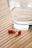 Glass of Water and Medicine Capsules Royalty Free Stock Photo