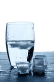 Glass of water and melting ice cubes on a wooden table. Royalty Free Stock Photography