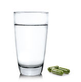 Glass of water and moringa capsule pills on white background Royalty Free Stock Photography