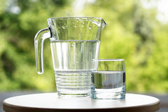 Glass Of Water. Near jug on green nature background royalty free stock image