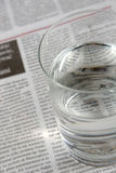 Glass of water on a newspaper. Letters could be seen through the glass. Shallow DOF Stock Image