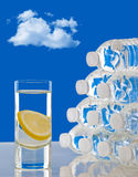 Glass of water next to bottles of water Royalty Free Stock Photos