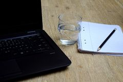 Glass of water, notebook, pencil and laptop royalty free stock image