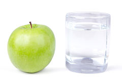 Glass of water and one green apple Stock Image
