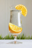 Glass of water with orange on a white background. With grass Royalty Free Stock Photography