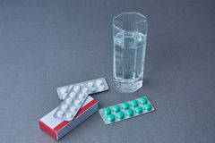 The Glass of water and packs of pills. Royalty Free Stock Photo
