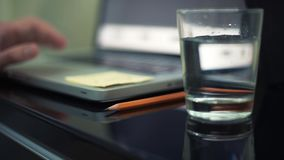 Close up of glass of water and pencil on table. Young man using laptop in cafe. Glass of water and pencil on table. Young man using laptop in cafe. Analyzing stock video footage