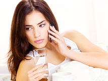 Glass of water and phone in bed Royalty Free Stock Images