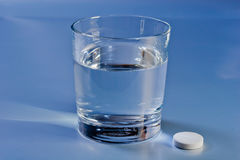 Glass of water and a pill Stock Images