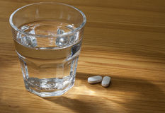 Glass of Water and Pills. Glass of Water and Pills on the wooden table. With reflect of light Stock Photography