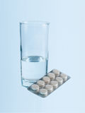 Glass of water and pills Stock Photos