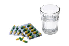 Glass of water and pills capsules Royalty Free Stock Images