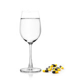 Glass of water and pills capsules on white background Stock Photos