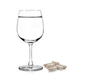 Glass of water and pills capsules  on white background Royalty Free Stock Image