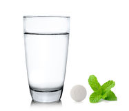 Glass of water pills and mint on white background Stock Image