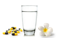 Glass of water pills and Tropical flowers frangipani Stock Images