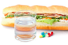 Glass of water, pills and two hot dogs with various ingredients. Glass of water with pills and two hot dogs with various ingredients. Isolated on grey Royalty Free Stock Image