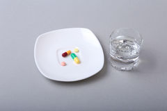 Glass of water and pills on white background Royalty Free Stock Photography
