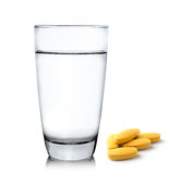 Glass of water and pills  on white background Royalty Free Stock Images