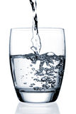 Glass of Water. Water pouring into a glass, isolated on white background Stock Image