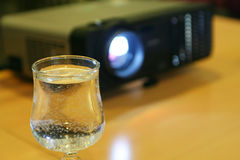 Glass of water with projector behind (horizontal). Glass of water on table with projector behind (horizontal Stock Photography