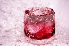 Red splashes in the glass of water. Glass of water with red jelly Royalty Free Stock Image
