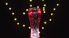 Glass of water in red light is turning. Blue cocktail. Bar concept.  stock video footage