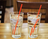 Glass of water with red straw on wooden table. Picture of iced water in transparent glass with red straw light refraction on wooden table at restaurant Stock Photo