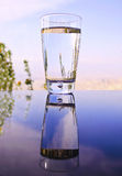 Glass with water reflection on table Stock Image
