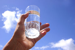 Glass Water Sky. Hand holding glass of purewater up to the sky Stock Image