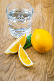 Glass of water and sliced fresh lemon Stock Photos