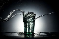Glass with water splash Stock Images