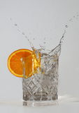 Water Splashing from a Crystal Glass. Water splashes from the crystal glass as an ice cube is dropped in. A slice of orange adds a splash of colour Royalty Free Stock Photo