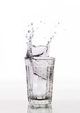 Glass of water splash. On a white background Royalty Free Stock Image