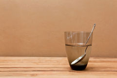 Glass of water and spoon on wooden table. Stock Photo