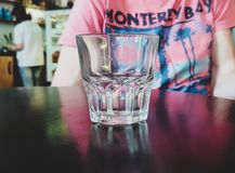 Glass of water standing on a table against the background of the person royalty free stock images