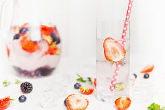 Glass with water and Strawberry. Summer drink with berries and ice cubes. Detox drink Stock Photos