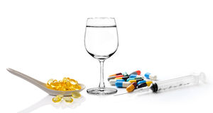Glass of water  syringe and colorful pill and capsules fish oil Royalty Free Stock Image