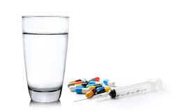 Glass of water  syringe and colorful pill and capsules on white Royalty Free Stock Images