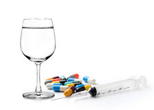 Glass of water  syringe and colorful pill and capsules Royalty Free Stock Photo