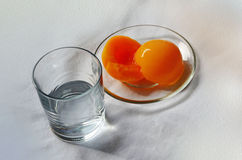 Glass with water and syrup peaches. Glass of water and the two halves of the peach in syrup on a transparent plate on a light background Stock Photo