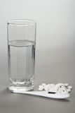 Glass with water, tablets and thermometer Royalty Free Stock Photos