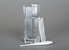 Glass with water, thermometer and powders Royalty Free Stock Photography