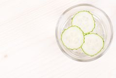 A glass of water with three slices of fresh cucumber on a light Stock Image