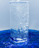 A glass of water, water with bubbles overflows through glass. The glass of water, water with bubbles overflows through glass Royalty Free Stock Image
