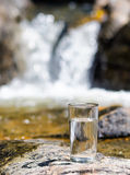 Glass of water by waterfall Stock Image