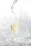 Glass Of Water on white. Yelllow drink being poured in a transparent glass with splashes on white Stock Image