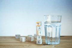 Glass of water with wooden blocks Royalty Free Stock Photos
