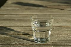 Glass of water on wooden table Stock Image