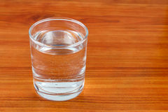 Glass of water on wooden table with space for text Royalty Free Stock Image